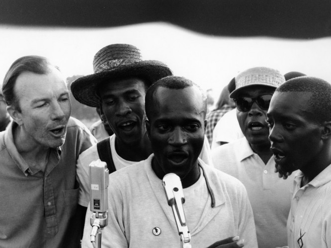 "American folk singer Pete Seeger and civil rights activists in Greenwood, Mississippi, in 1963, sing ""We Shall Overcome"", a traditional African-American hymn that later became emblematic of the civil rights movement in the United States. Photo by Adger Cowans/Getty Images."